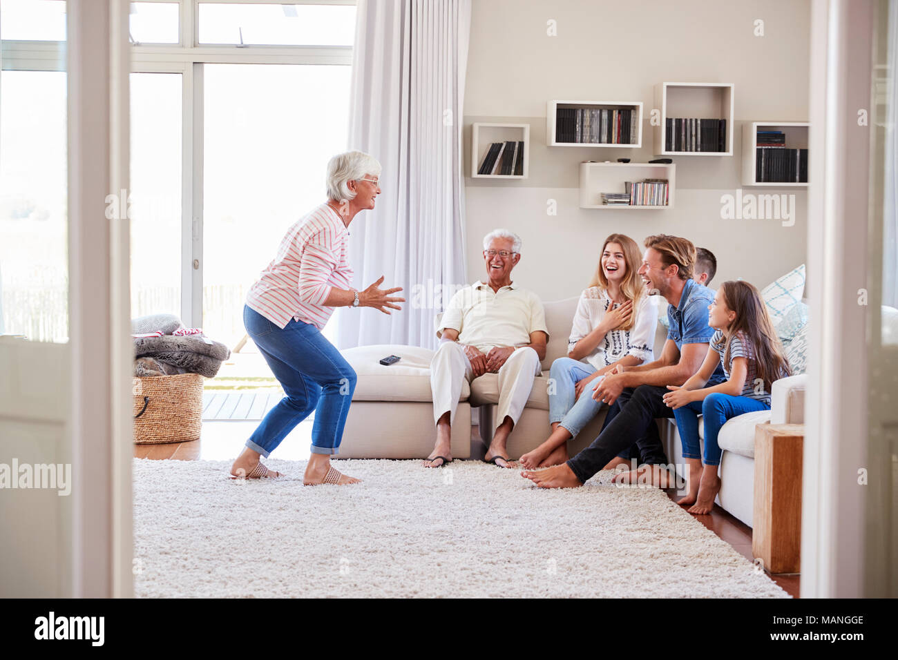 Multi Generation Family Sitting On Sofa At Home Playing Charades Stock Photo