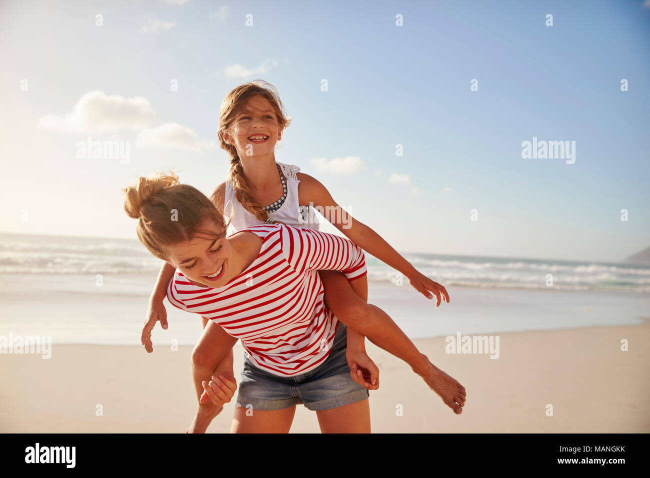 Mother Carrying Daughter On Shoulders On Beach Vacation - Stock Image