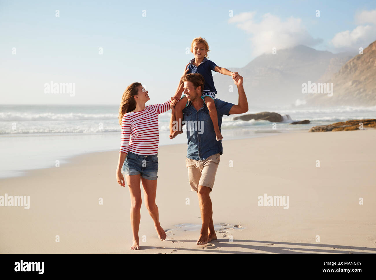 Parents Carrying Son On Shoulders On Beach Vacation - Stock Image