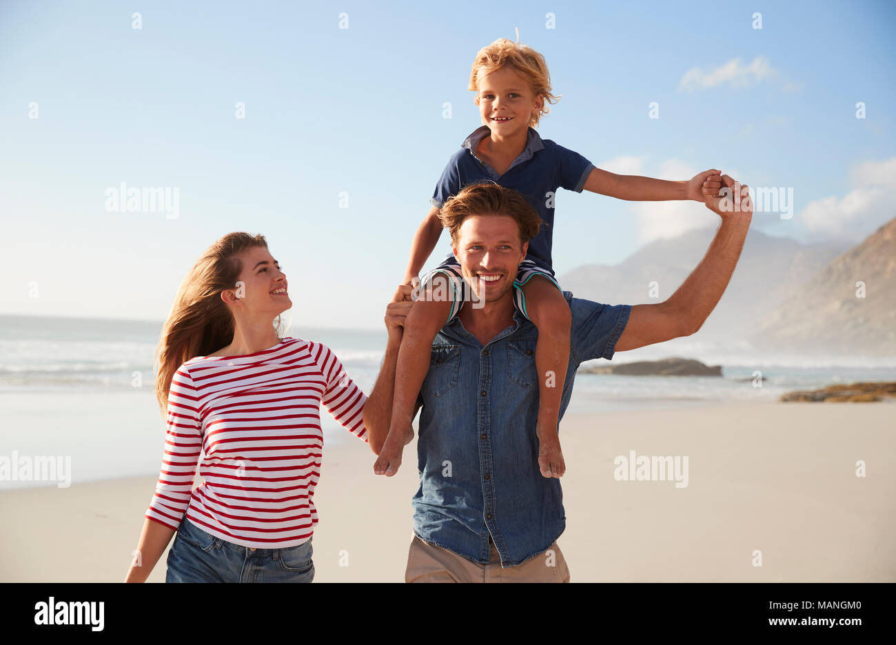 Portrait Of Parents Carrying Son On Shoulders On Beach Vacation - Stock Image