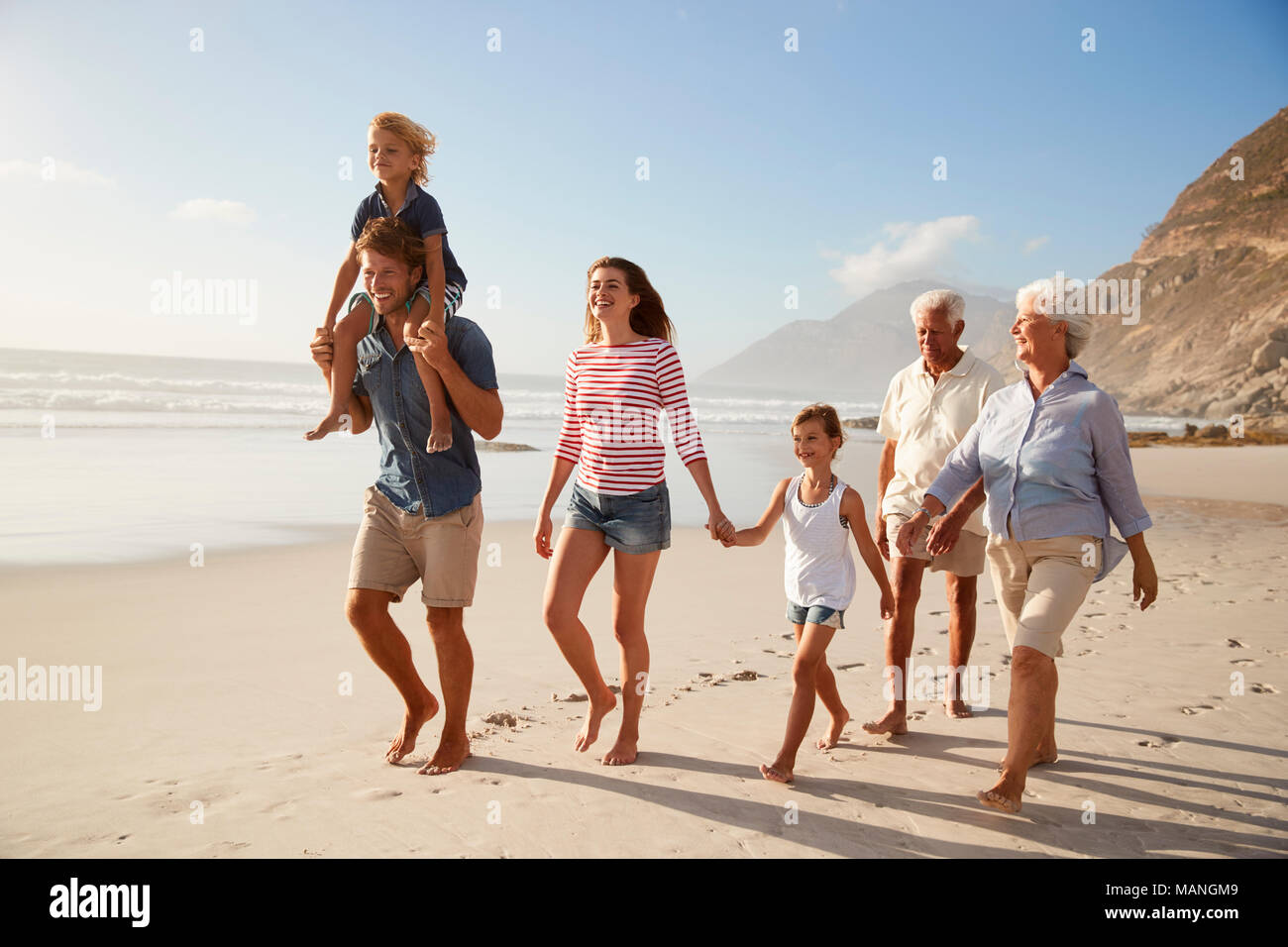 Multi Generation Family On Vacation Walking Along Beach Together - Stock Image