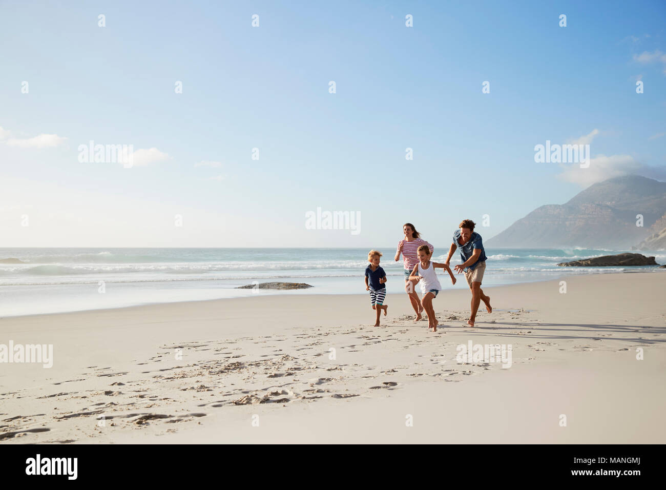 Parents Running Along Beach With Children On Summer Vacation - Stock Image