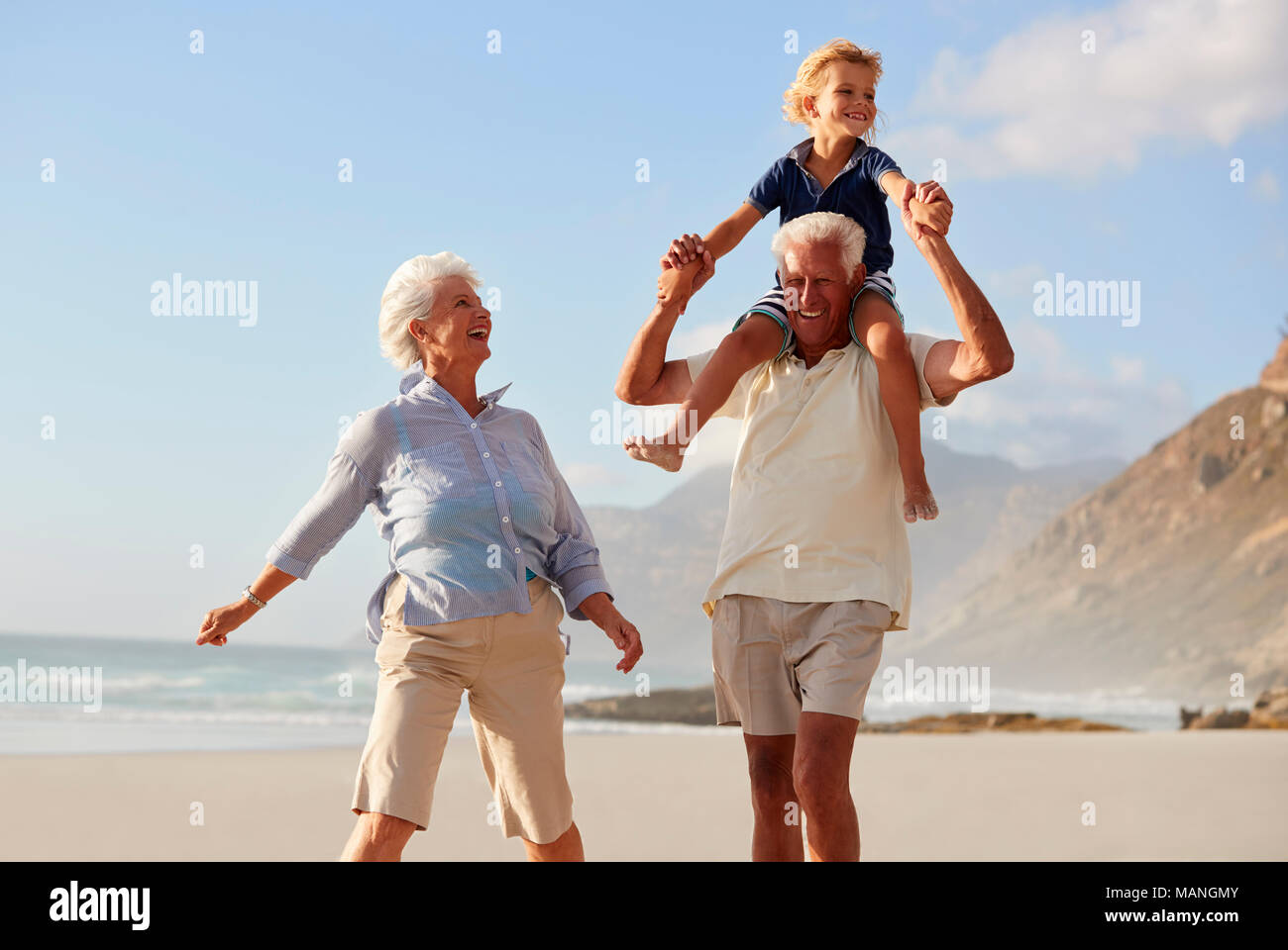 Grandparents Carrying Grandson On Shoulders On Walk Along Beach Stock Photo