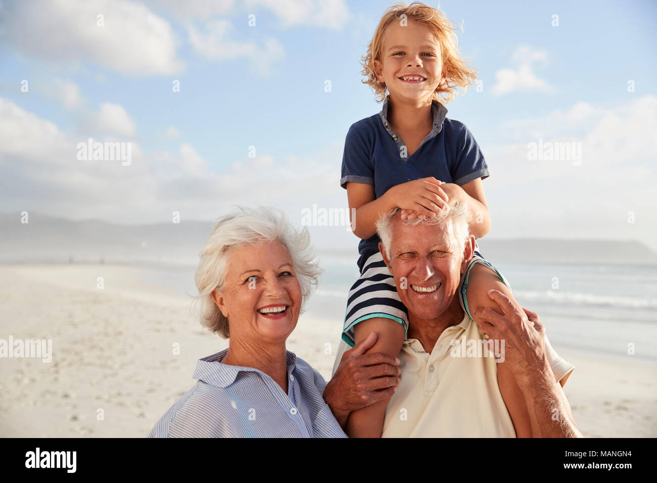 Grandparents Carrying Grandson On Shoulders On Walk Along Beach - Stock Image