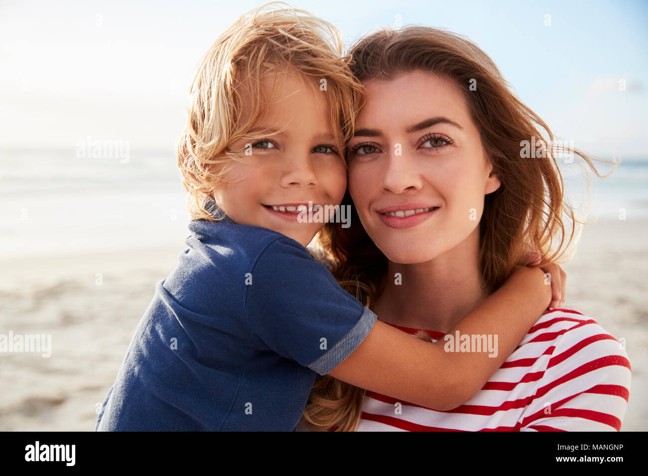 Portrait Of Mother Hugging Son On Summer Beach Vacation - Stock Image