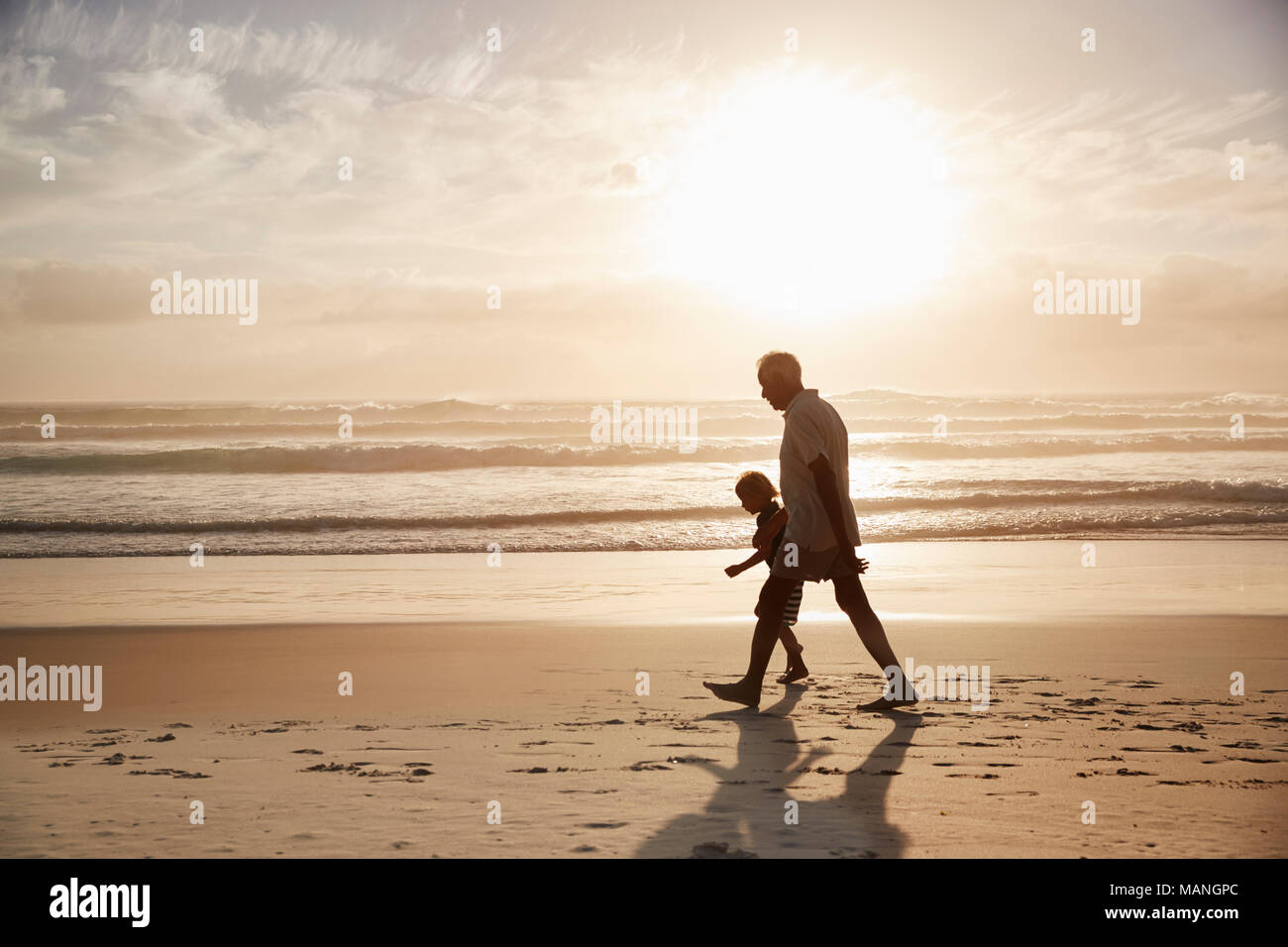 Silhouette Of Grandfather Walking Along Beach With Grandson - Stock Image