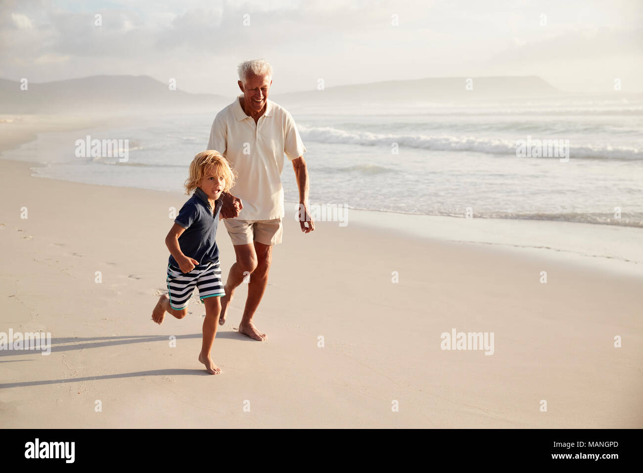 Grandfather Running Along Beach With Grandson On Summer Vacation - Stock Image