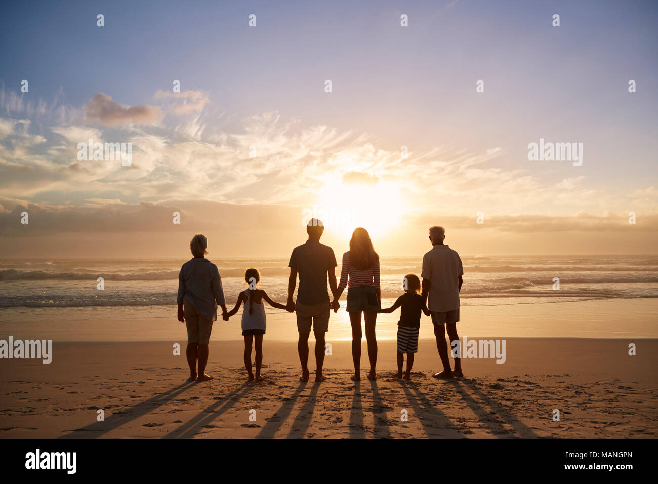Rear View Of Multi Generation Family Silhouetted On Beach - Stock Image