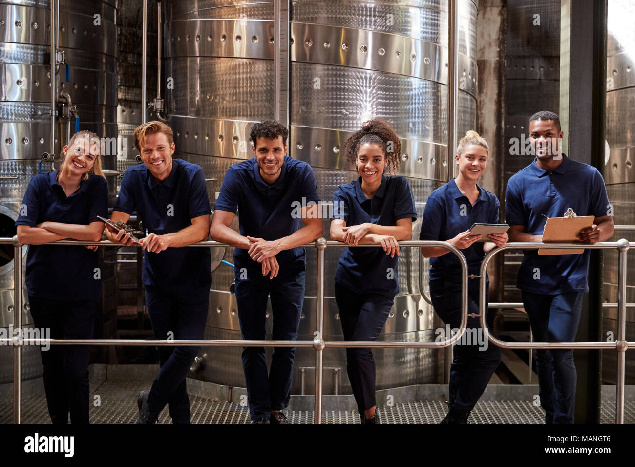 A row of staff at a wine factory smiling to camera, close up Stock Photo