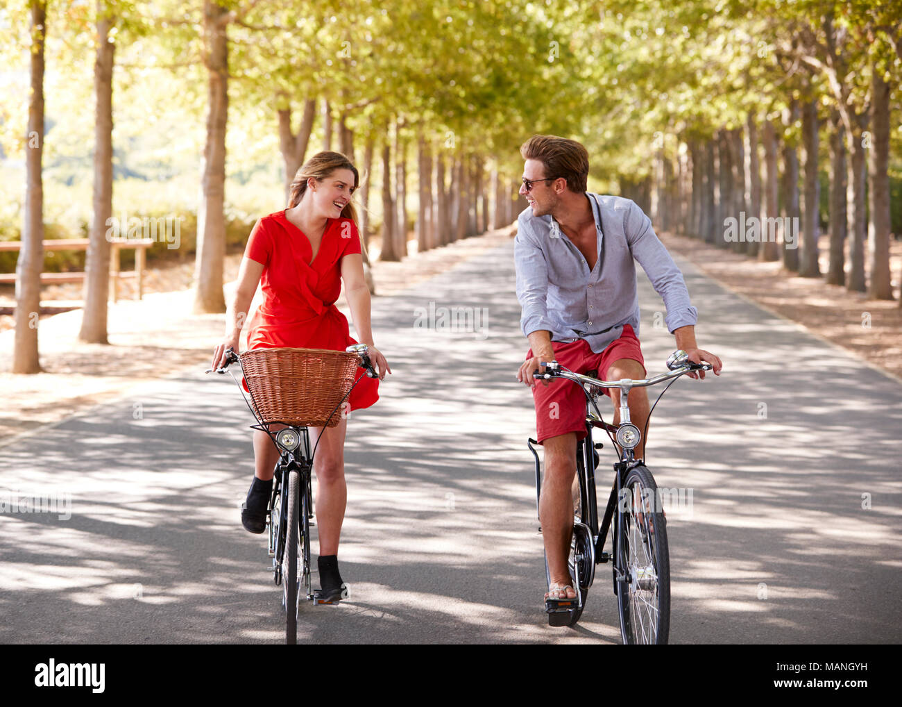 Couple riding bikes on an empty road looking at each other - Stock Image