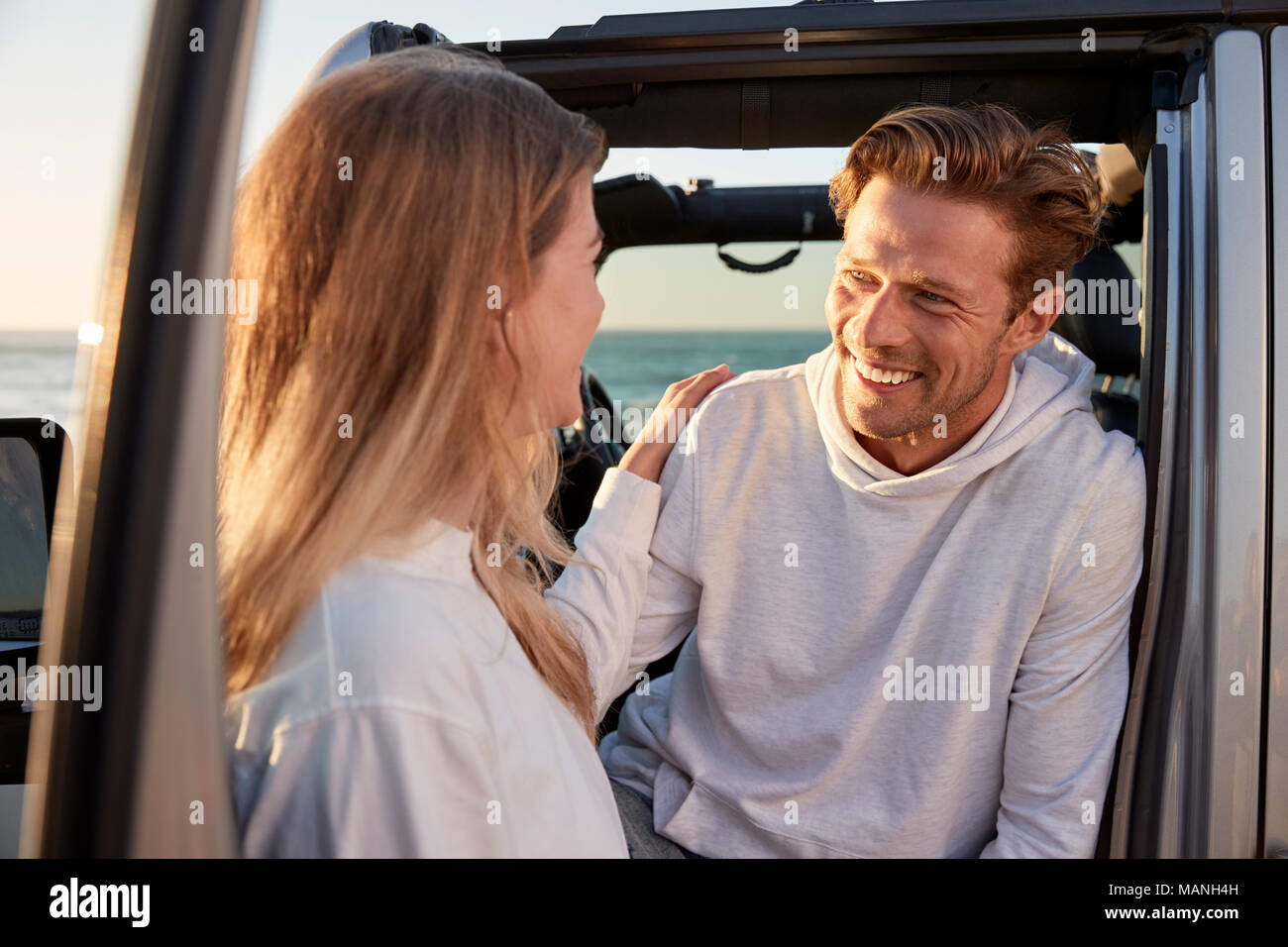 Young couple looking at each other by car, close up - Stock Image