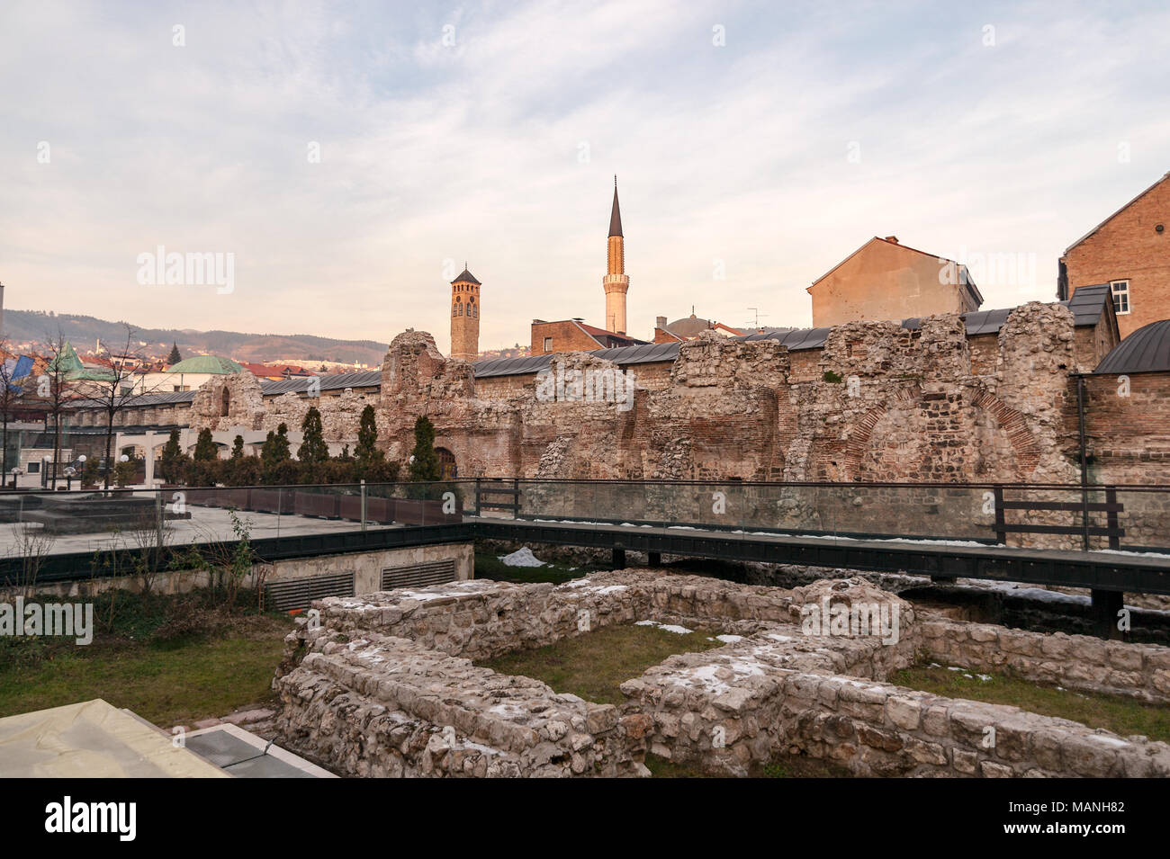 SARAJEVO, BOSNIA - JAN 25 2018: Historical Taslihan ruins with the old watch tower and minaret of Gazi Husrev mosque at the background. Ruins are a next to Sarajevo Europe Hotel. - Stock Image