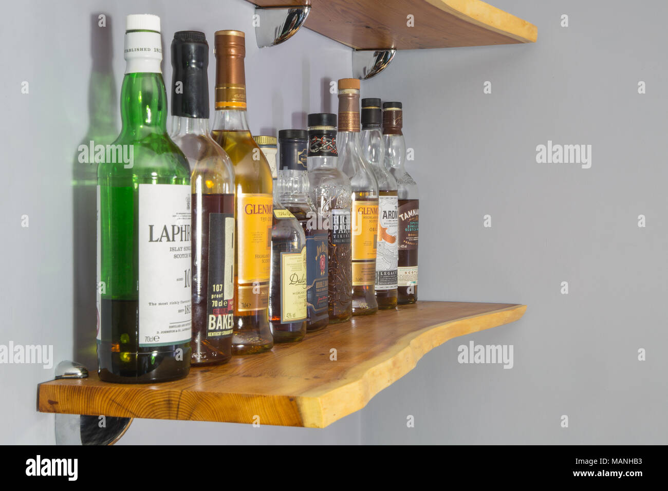 A collection of whisky (Irish spelling - whiskey) on a shelf made of ...