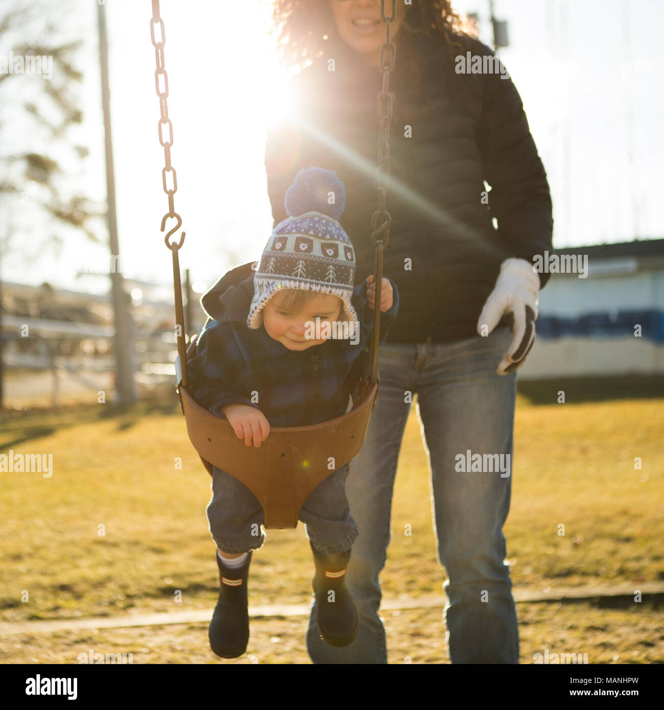 Smiling Mommy and Happy Boy Swing in the early Spring sunshine at local park. Brings good feelings of nostalgia and warm childhood memories. - Stock Image