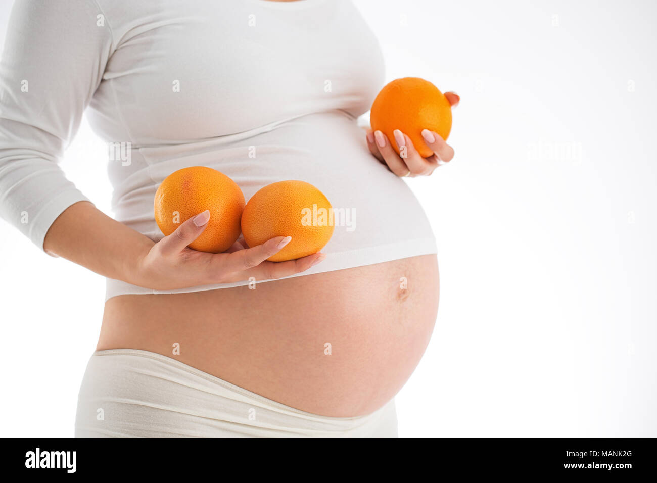 Pregnancy and heathy eating concept. Pregnant woman holding fresh oranges isolated on white background. - Stock Image