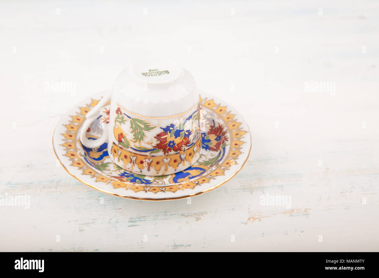 Upside down vintage Turkish coffee cup over saucer traditionally using for fortune telling on wooden table , high angle view , coffee fortune telling  - Stock Image