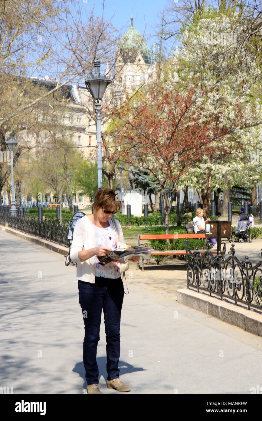 Woman / lady reading a tourist guide book while sightseeing around the Hungarian  capital city of Budapest Hungary in spring time - Stock Image