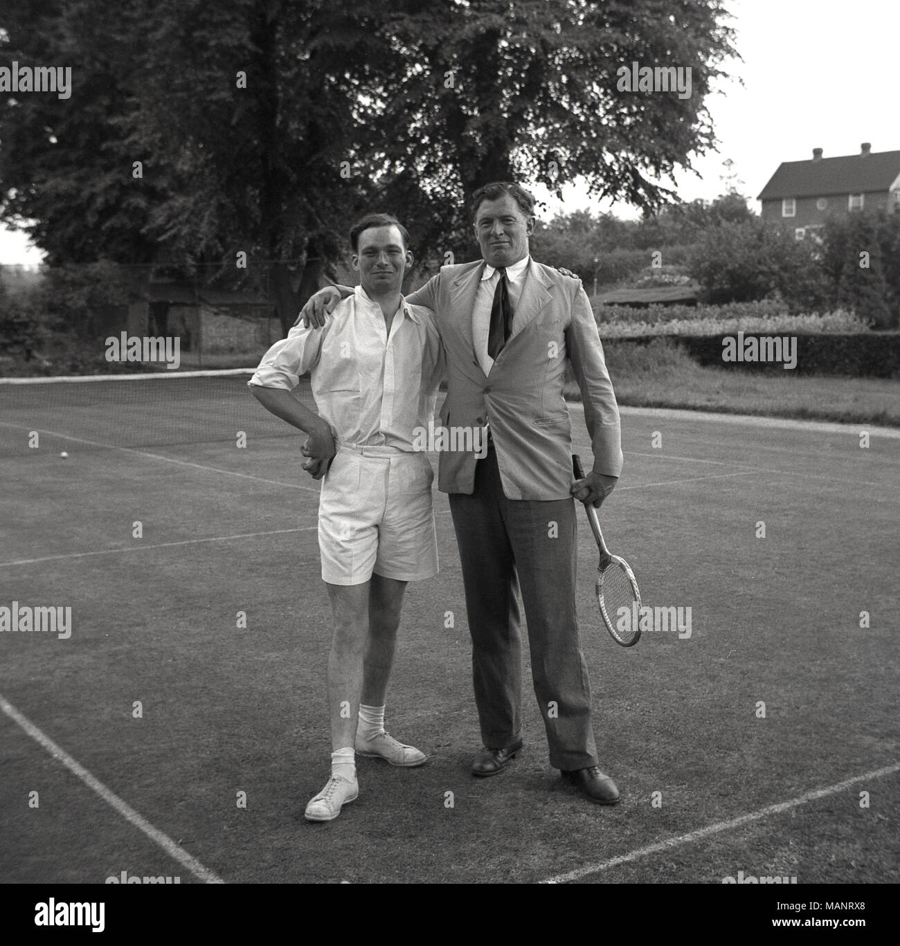 1954, historical, two men pose for a picture standing on a grass-court tennis court at the Bonham-Carter's country-house, Wyck Place, near Alton, Hampshire, England, UK. - Stock Image