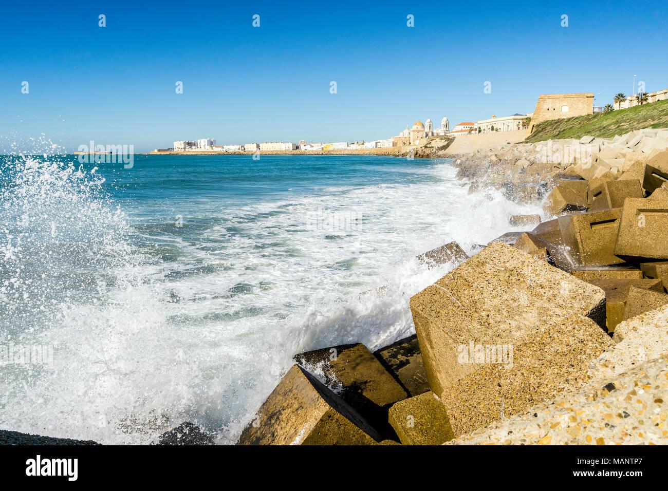 Atlantic waves breaking on the urbanized shore of old Cadiz, Andalusia, Spain - Stock Image