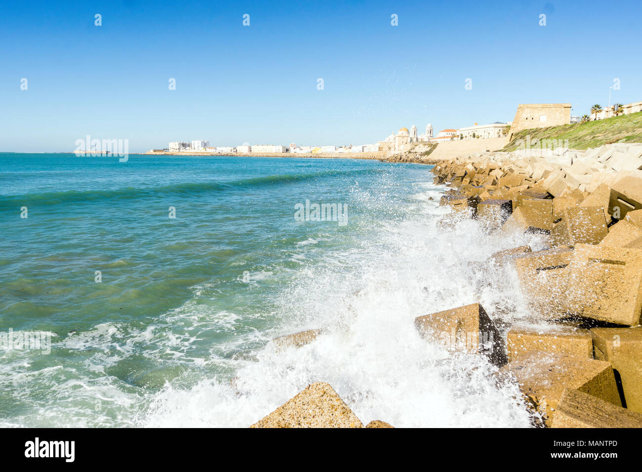 Atlantic waves breaking on the urbanized shore of old Cadiz, Andalusia, Spain - Stock Image