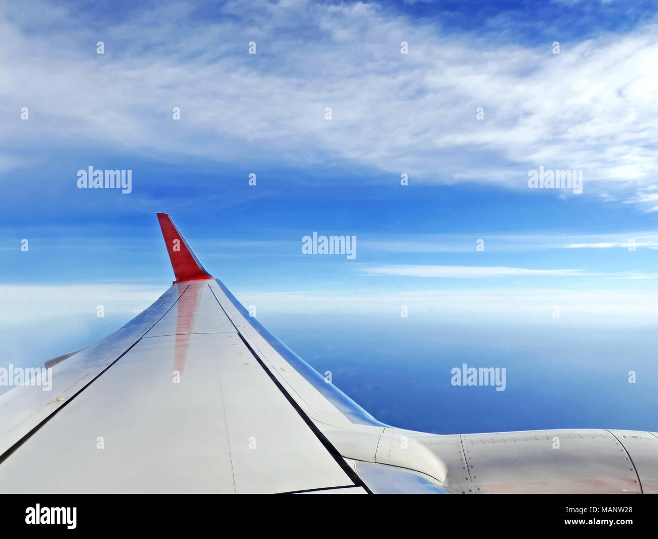 Airplane view, traveling by plane. View outside an airplane window to the airplane wing and blue sky and sea. - Stock Image