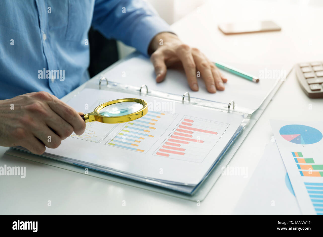 internal audit concept - man with magnifying glass inspecting business documents - Stock Image