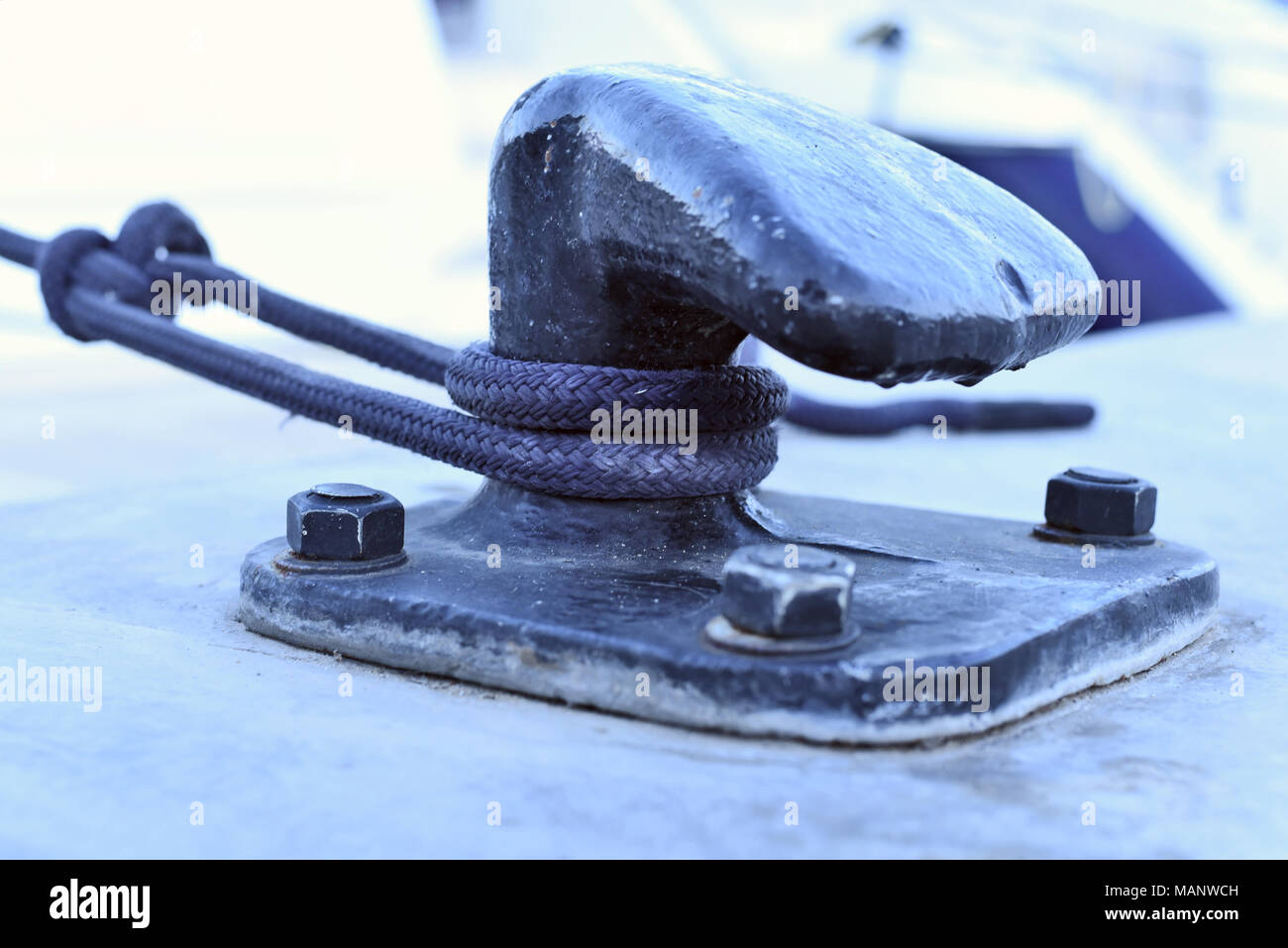 Harbor scene with focus on a rope or anchored boat on a pier. Detail shot. - Stock Image