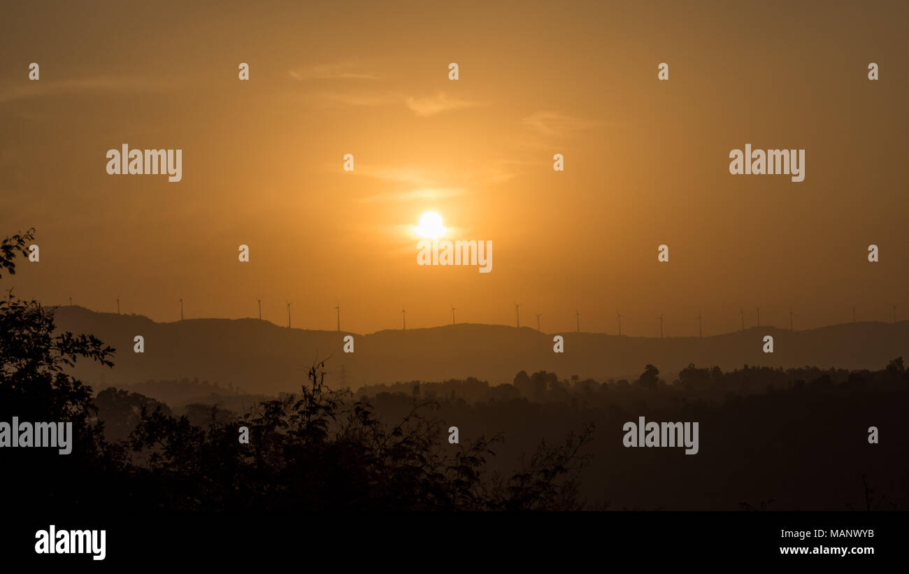 Sunrise over the Mountains of Nilshi with windmills on the horizon - Stock Image