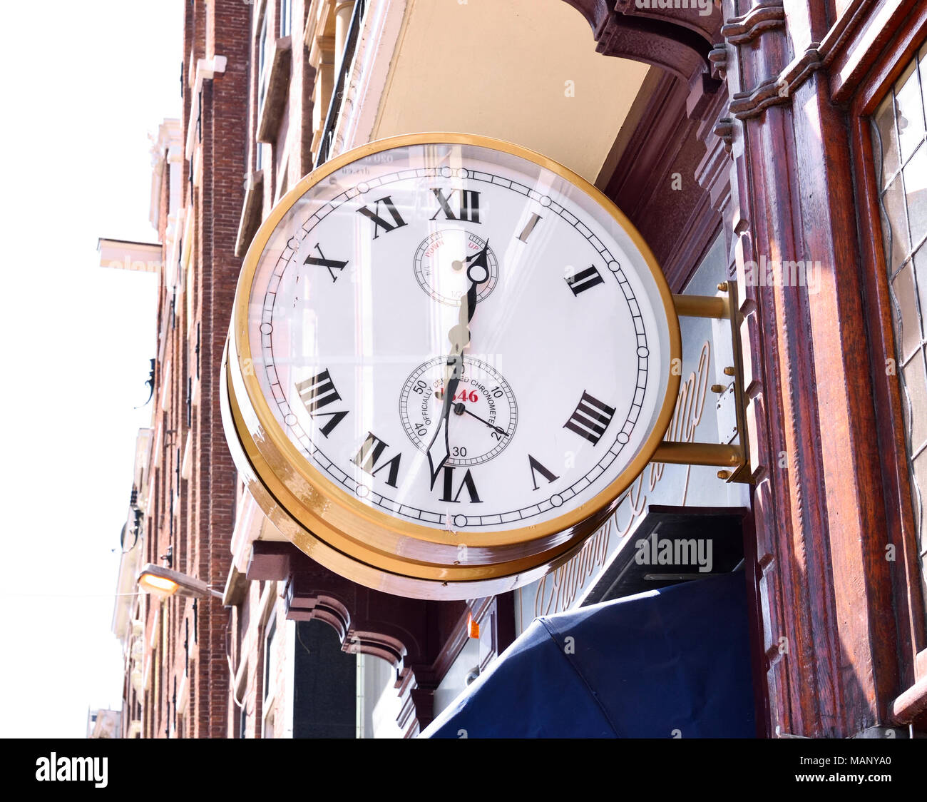 Old or antique clock on a house facade or building exterior. Beautiful golden clock. - Stock Image