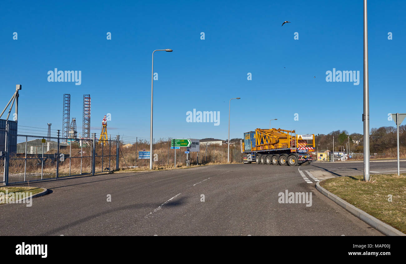 A Multi wheeled heavy Lift Lorry and Trailer turn into the Southern Entrance of Dundee Port from Broughty Ferry road, in Angus, Scotland. - Stock Image