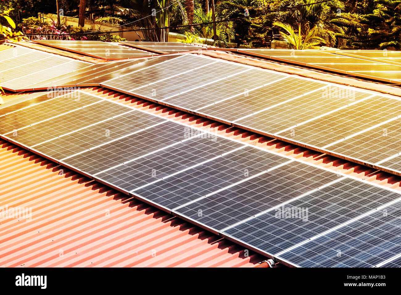 Roof with solar panels fragment under sunny blue sky. sun is shining on black solar panels. Alternative energy source. Electrification in the Andaman  - Stock Image