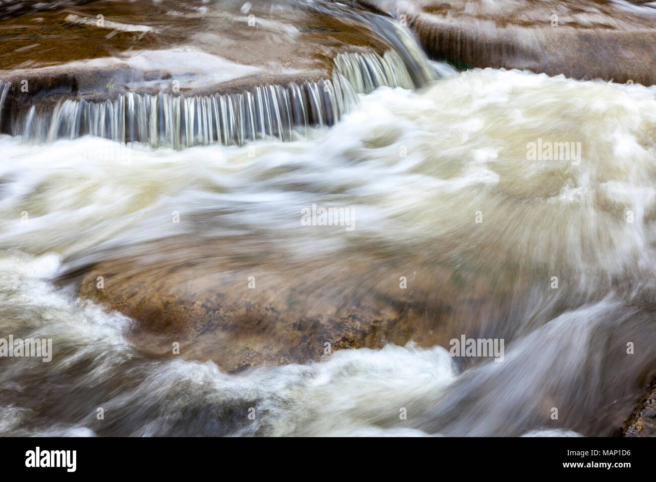 Closeup of rushing water over rocks in a creek. - Stock Image
