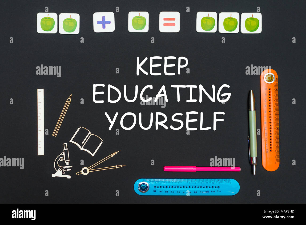 concept back to school, above stationery supplies and text keep educating yourself on black backboard - Stock Image