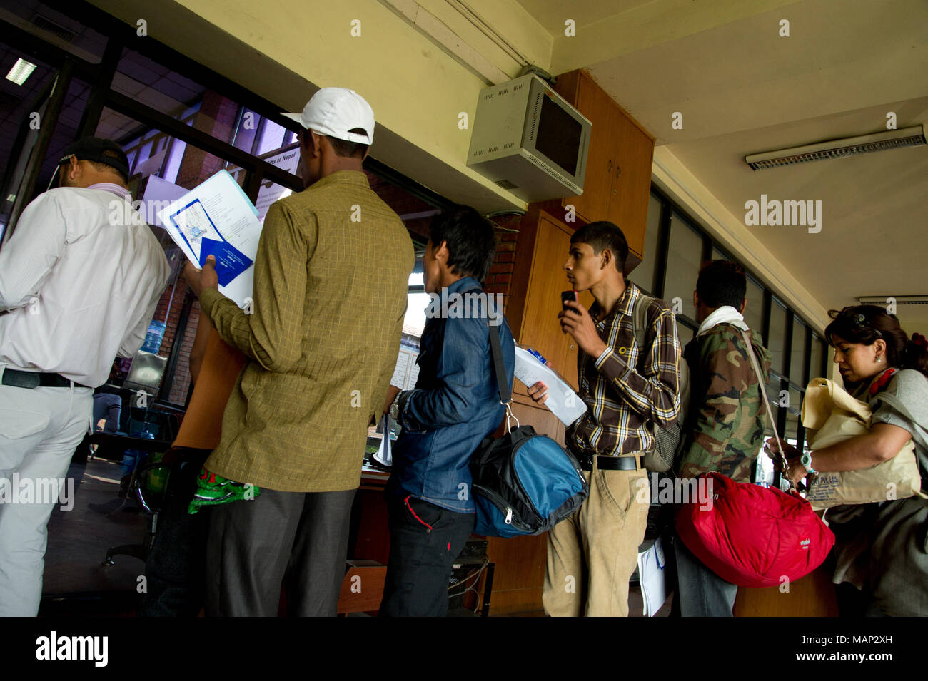 Nepal 2014. Kathmandu airport. Migrant workers about to travel to the Gulf, queing to board a flight to Doha, Qatar - Stock Image