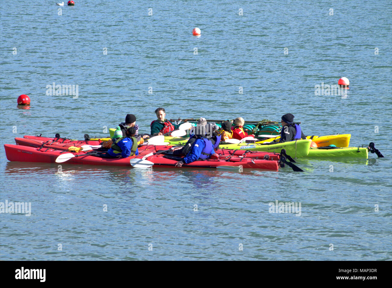 kayakers conoeists rafted up on the sea taking instructions from a water sport tutor in castlehaven harbour, a popular holiday destination.Ireland - Stock Image