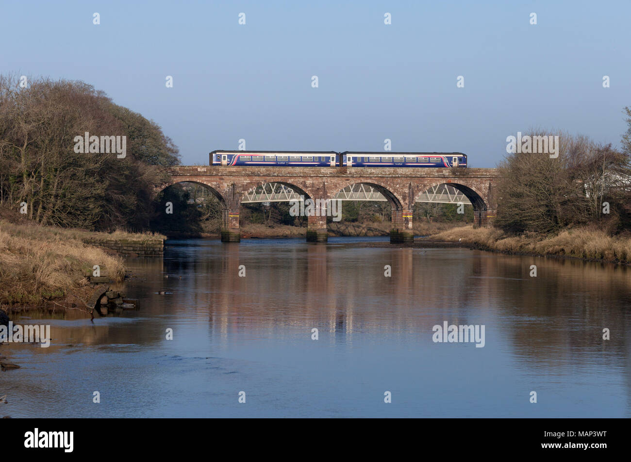 Scotrail class 156 sprinter train crosses the viaduct at  Annan (River Annan, South of Dumfries) reflected in the river below - Stock Image