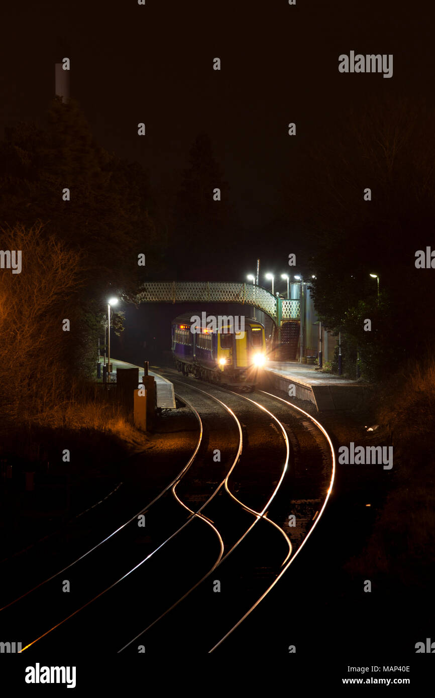 An Arriva Northern rail sprinter train calls at  Dalston railway station  on the Cumbrian coast railway line in the dark at night - Stock Image