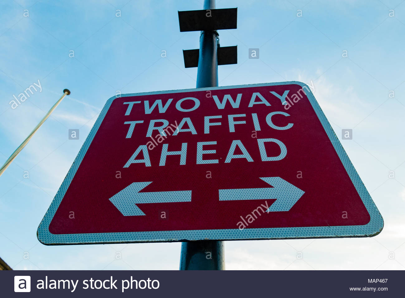 Two way traffic ahead sign, white reflective lettering on a red background, Southport, Merseyside England UK Stock Photo