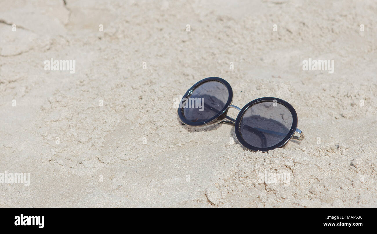 d56bb02816 Reflecting sunglasses on the beach, glasses in the sand. - Stock Image