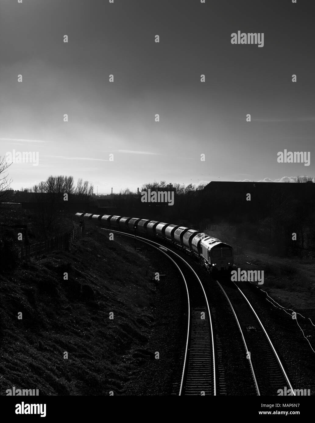 A Freightliner class 66 locomotive at South Bank (Teeside) with a freight train of empty rock salt wagons heading to Boulby - Stock Image