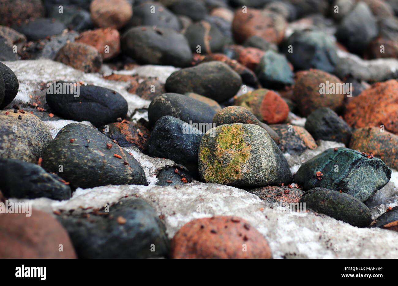 Colorful rocks laying on a ground. In between the stones there is some snow and ice. Photo is taken in Finland during spring season. Stock Photo