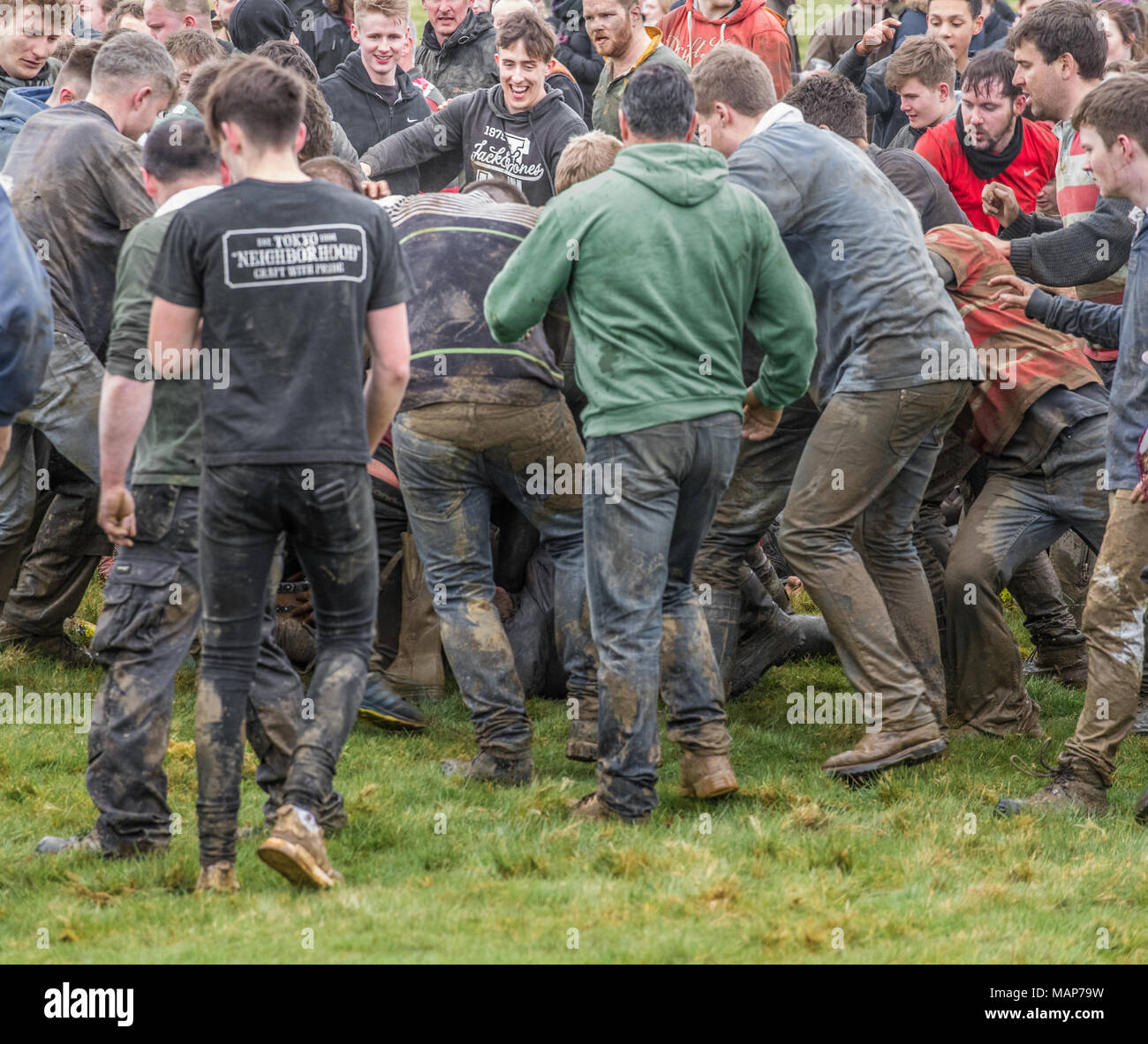 Villagers from Hallaton tussle with rival villagers from the nearby village of Medbourne in a rough encounter on  wet and muddy countryside in the hea - Stock Image