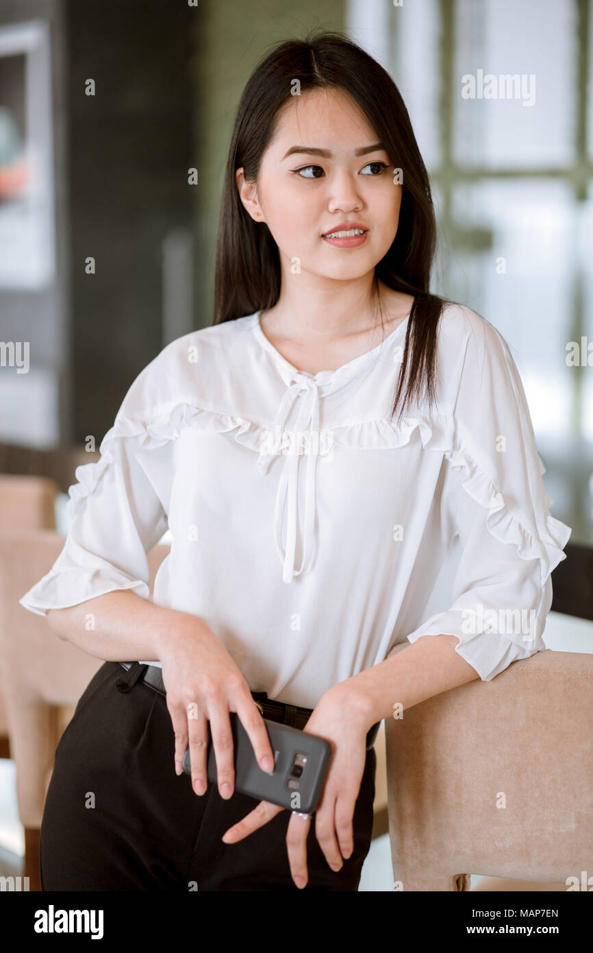 Asian woman with black long straight black hair wearing white blouse - Stock Image