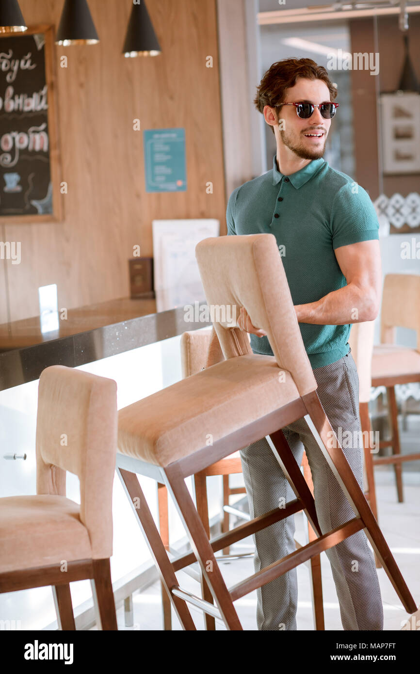 man in glasses and blue T-shirt and grey trousers holding chair. - Stock Image