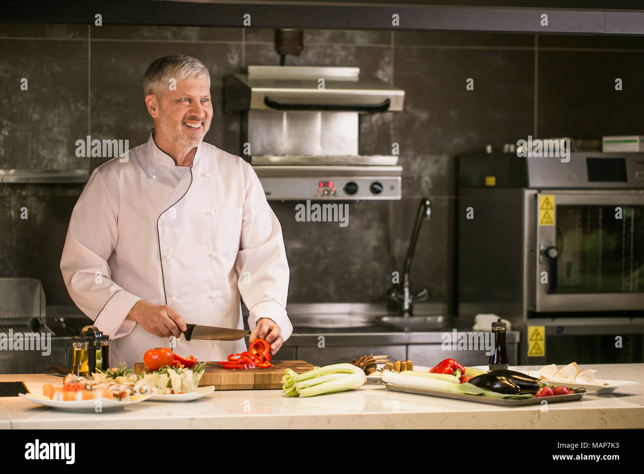 happy old cook with grey hair is preparing a meal with pleasure - Stock Image