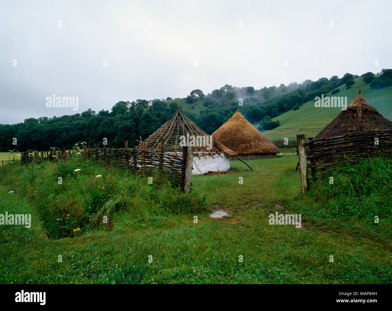 Archaeological reconstructions of Iron Age roundhouses seen through the NE entrance of a ditched and fenced enclosure at Butser Ancient Farm, UK. - Stock Image