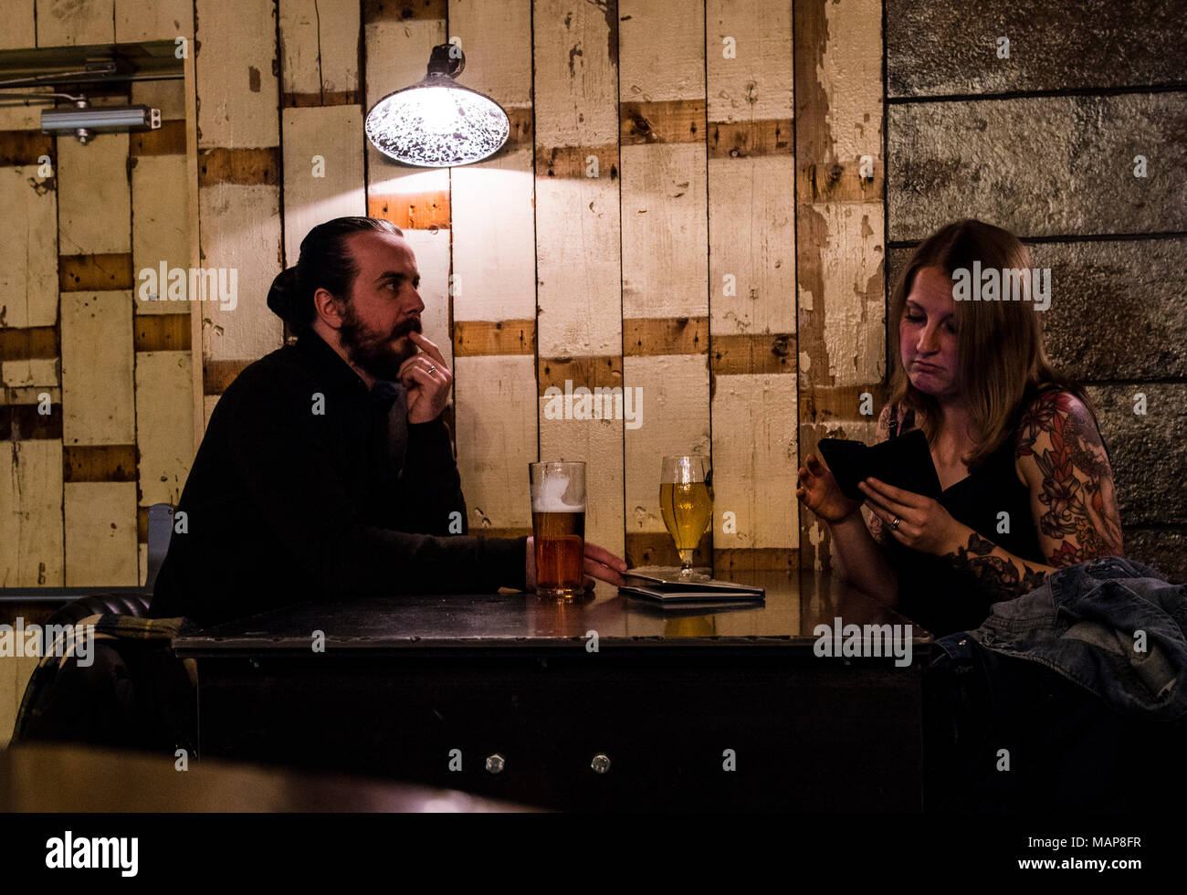 Woman on cell phone in bar with man watching - Stock Image