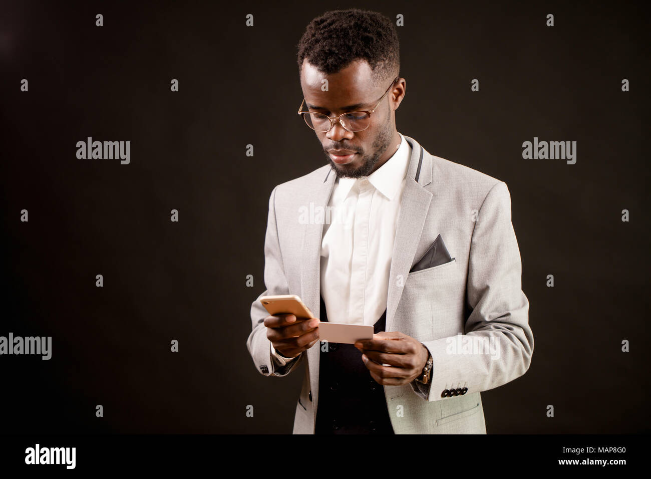african man holding sheet of paper and smart phone and dialing a number - Stock Image