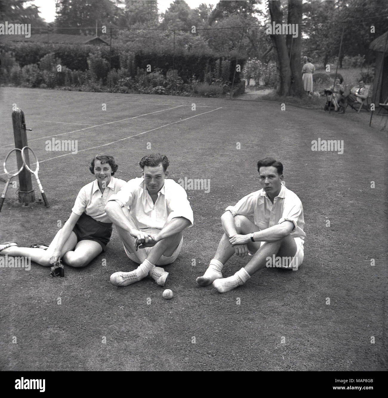 1954, historical, players sitting on the grass, relaxing afer a game of lawn tennis at the Bonham-Carter's country-house, Wyck Place, near Alton, Hampshire, England, UK. - Stock Image