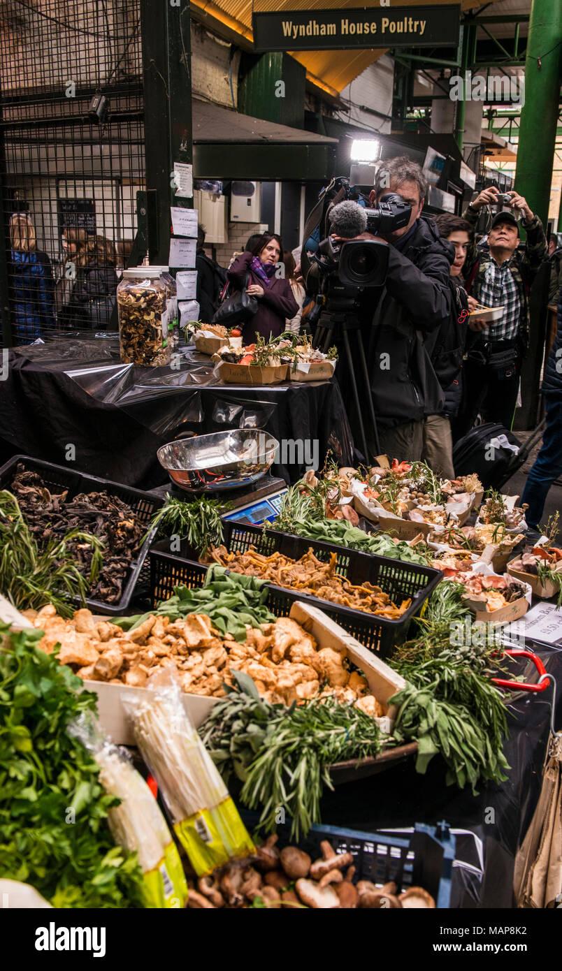 Fresh produce on market stall with camera man, Borough Market, Southwark, London, England, UK - Stock Image